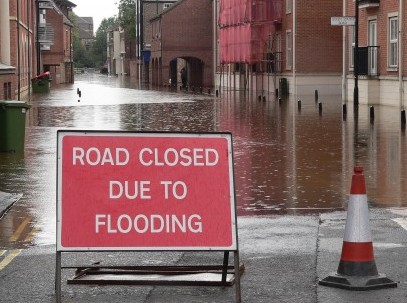 Road closed due to flooding caused by householders paving over their front gardens